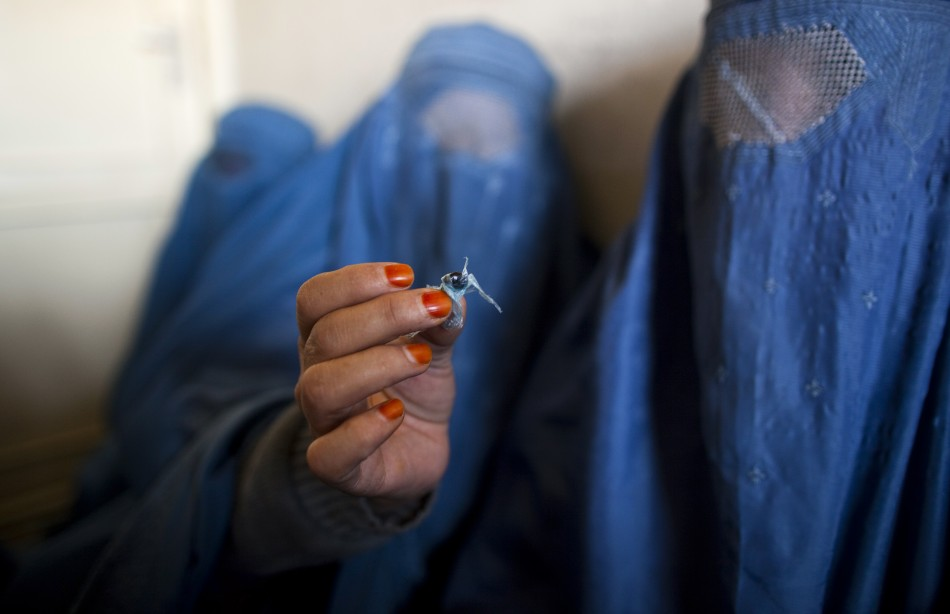 An Afghan woman holds up opium as she attends a counseling session at the Nejat drug rehabilitation centre, an organisation funded by the United Nations providing harm reduction and HIV/AIDS awareness, in Kabul