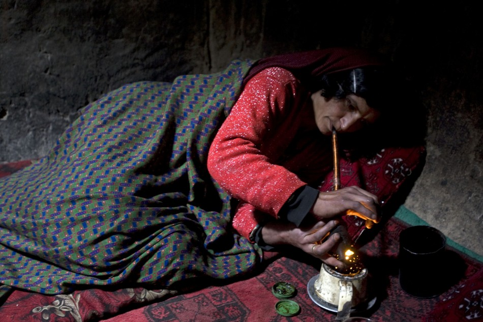 Naik Bakhat, a 35-year-old mother of four, smokes opium in her house in the Eshkashem district of Badakhshan province, northeast of Kabul April 24, 2008.