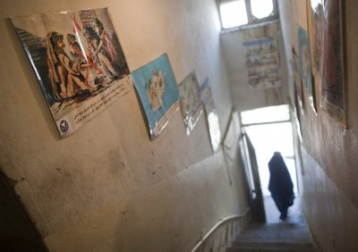 A woman clad in burqa walks out of the Nejat drug rehabilitation centre, an organisation funded by the United Nations providing harm reduction and HIVAIDS awareness, in Kabul