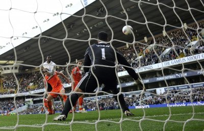 Tottenham Hotspur039s Emmanuel Adebayor rises above Swansea City039s Gary Monk to score his second goal during ttheir English Premier League soccer match in London
