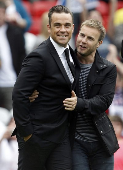 British singer Robbie Williams L walks onto the pitch with band mate Gary Barlow
