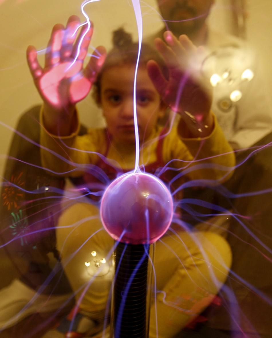 An autistic child touches an electric globe at the Consulting Centre for Autism in Amman