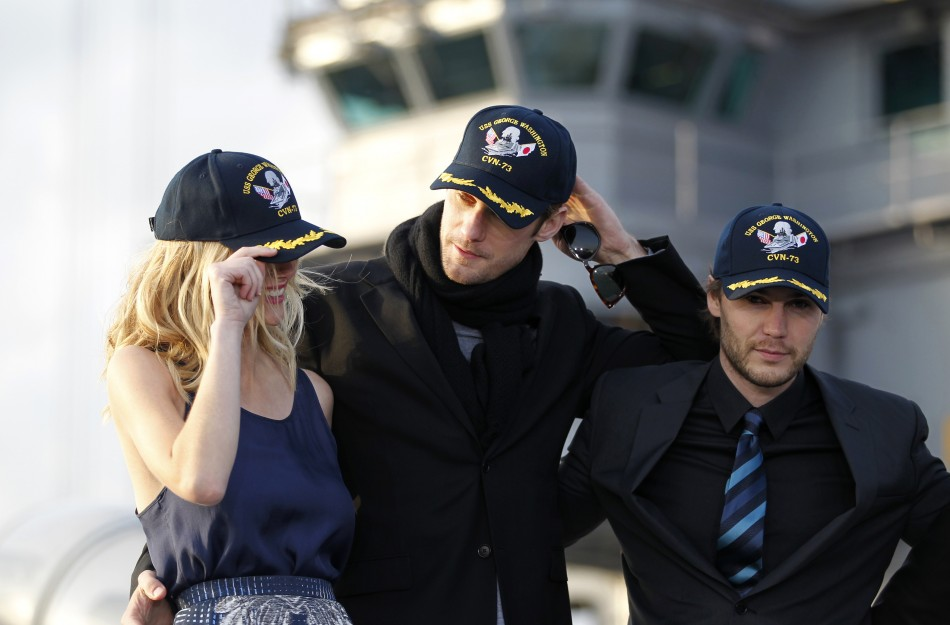 "Cast members of the film ""Battleship"" wear caps during a news conference atop a flight deck of aircraft carrier USS George Washington at Yokosuka port, south of Tokyo"