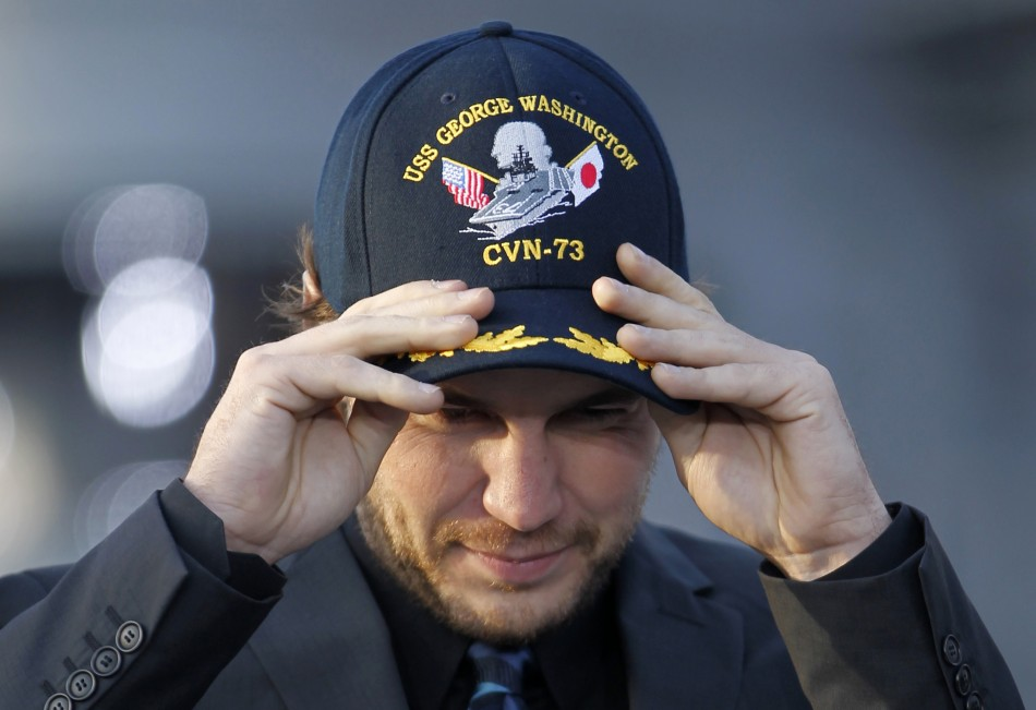 "Actor Taylor Kitsch wears a cap during a news conference to promote his film ""Battleship"" atop a flight deck of aircraft carrier USS George Washington at Yokosuka port, south of Tokyo"