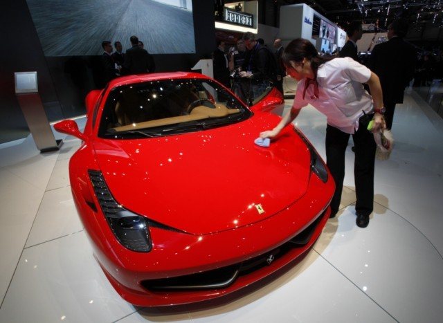 A staff cleans the Ferrari 458 Italia