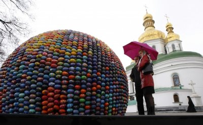 People look at a sphere sculpture made from Easter eggs on the day of its unveiling at Kievo-Pecherskaya Lavra cathedral in Kiev