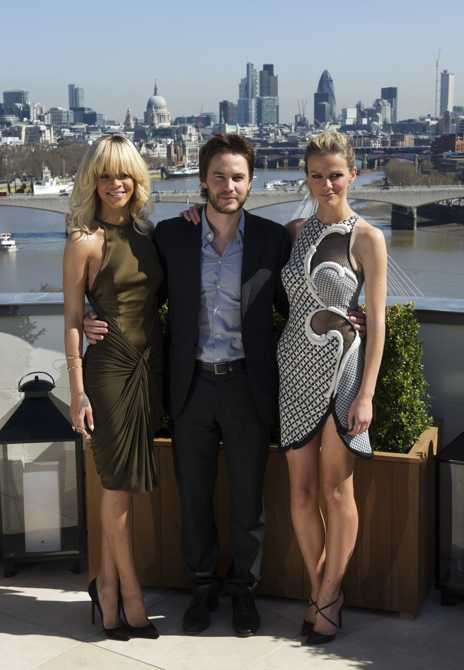 Singer Rihanna poses with Taylor Kitsch and Brooklyn Decker for a photograph during a media viewing to promote the film 'Battleship', at a hotel in central London