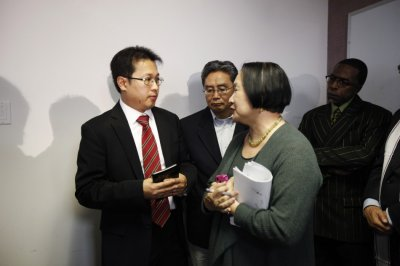Hyok-in Kwon and Kyung Kim of the Korean United Methodist Church speaks to Oakland Mayor Jean Quan during a news conference after a shooting incident at Oikos University in Oakland