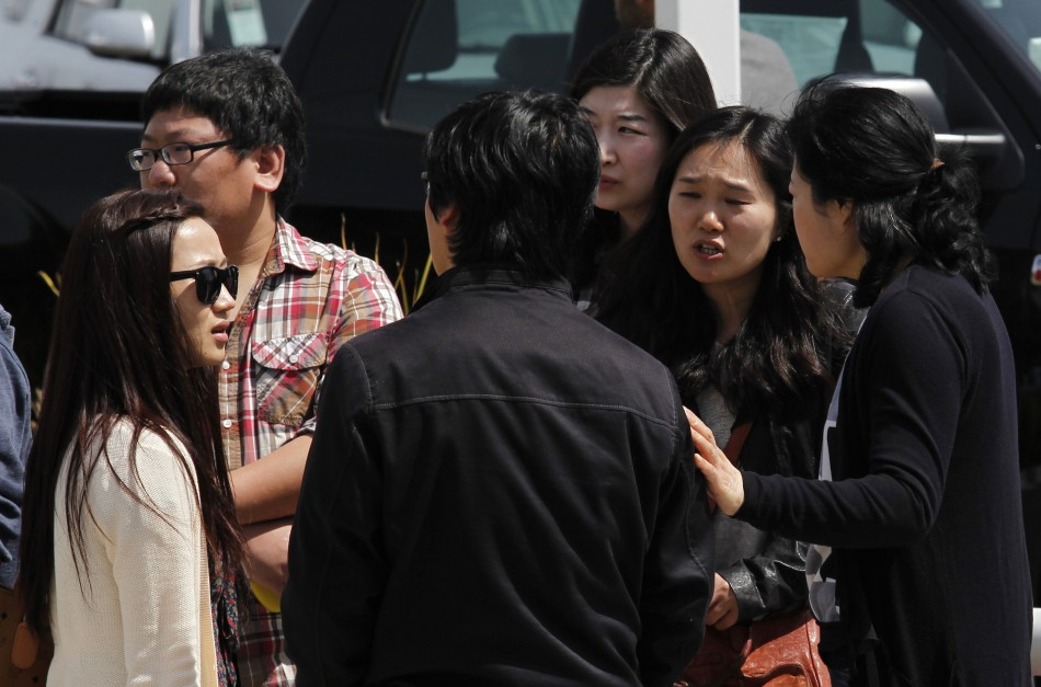 Students and onlookers at Oikos University talk amongst themselves at the scene of a multiple shooting at the school in Oakland, California