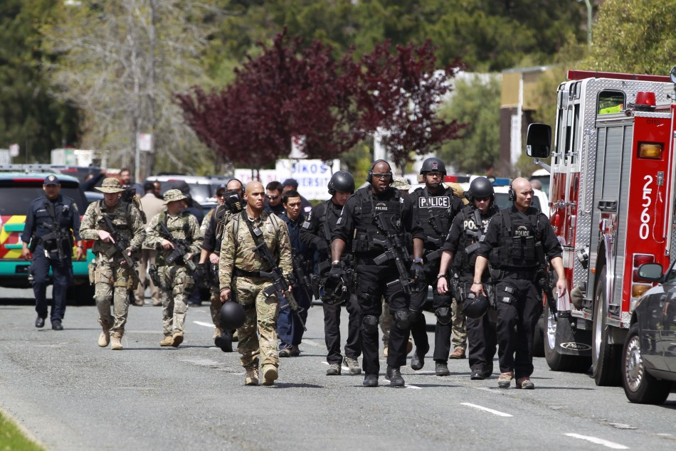Police officers walk on Edgewater Drive after a shooting at Oikos University in Oakland