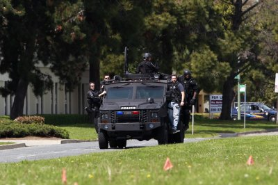Police officers on an armored vehicle survey the scene of a shooting at Oikos University in Oakland