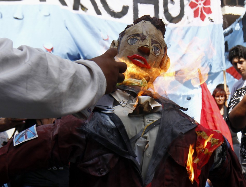 A man sets fire to an effigy depicting Prince William during a demonstration outside the British embassy in Buenos Aires (Reuters)