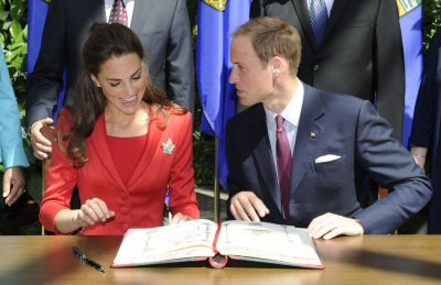 Britains Prince William and his wife Catherine, Duchess of Cambridge, react during a signing ceremony at the Calgary Zoo