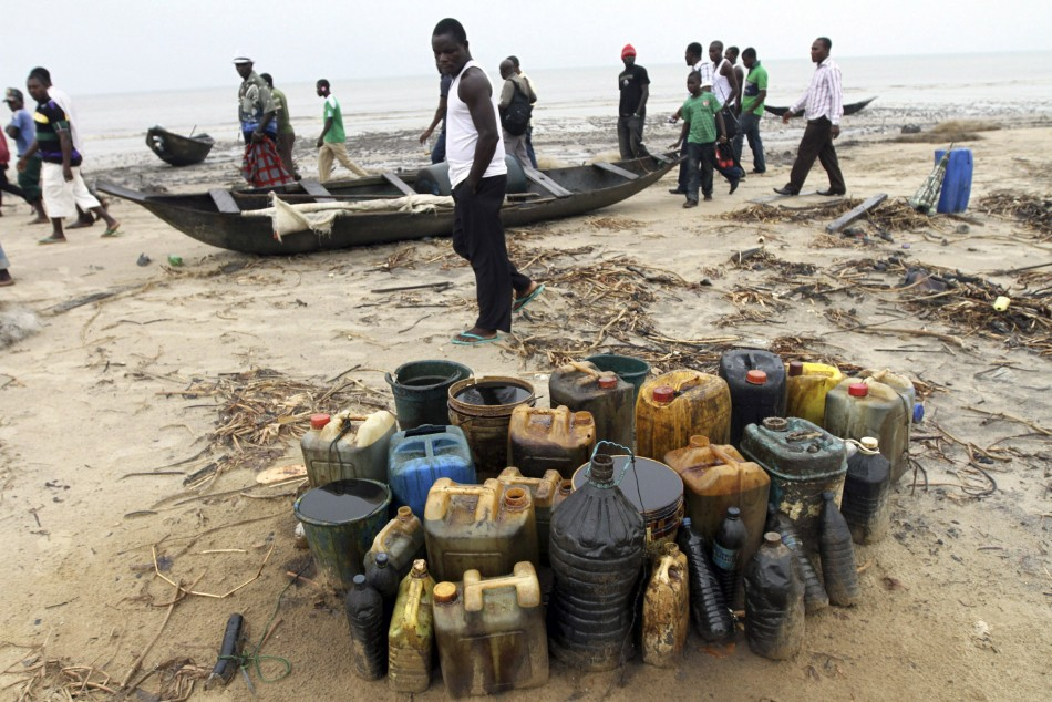 Villagers from Orobiri village walk past jerry cans of crude oil collected from a loading accident by Royal Dutch Shell on the Atlantic coast of Nigeria