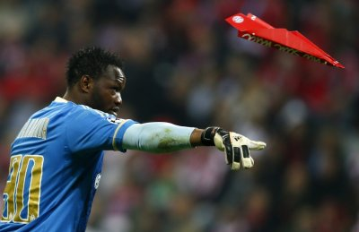 Goalkeeper Steve Mandanda of Olympique Marseille throws away a paper made plane thrown at him by Bayern Munich supporters during their Champions League quarter-final second leg soccer match in Munich