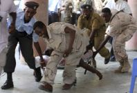 Soldiers carry the body of the chairman of Somali football federation after an explosion at the national theatre in Mogadishu