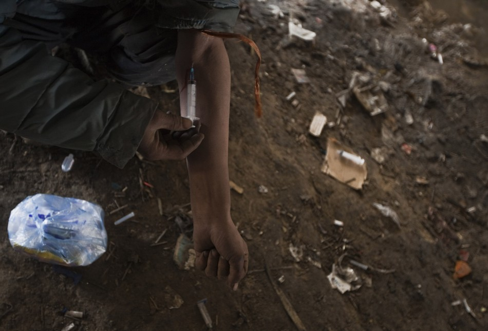 An Afghan drug addict injects himself under a bridge inhabited by fellow addicts in Kabul