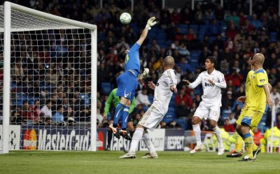 Real Madrid039s Varane and Pepe look at the ball as Ronaldo scores during their Champions League quarter-final second leg soccer match against APOEL at Santiago Bernabeu stadium in Madrid