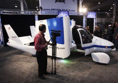 A man films aircraft company Terrafugias flying car, called the Transition, at the 2012 International Auto Show in New York
