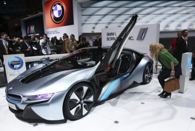 A visitor looks at the BMW i8 plug-in hybrid automobile at the 2012 International Auto Show in New York