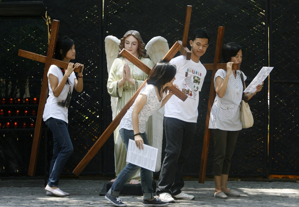 Catholic faithful carry crosses as they pray at the Stations of the Cross while doing Visita Iglesia on Maundy Thursday at a Church in Quezon City