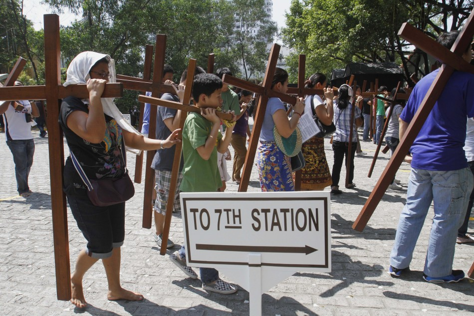 Catholic faithful carry crosses as they make their way to one of the Stations of the Cross while doing the Visita Iglesia on Maundy Thursday at a church in Quezon City