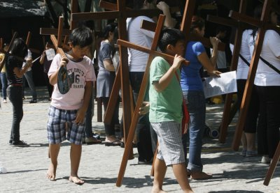 Children carry cross as they join their family members to pray at one of the Stations of the Cross while doing Visita Iglesia on Maundy Thursday at a church in Quezon City