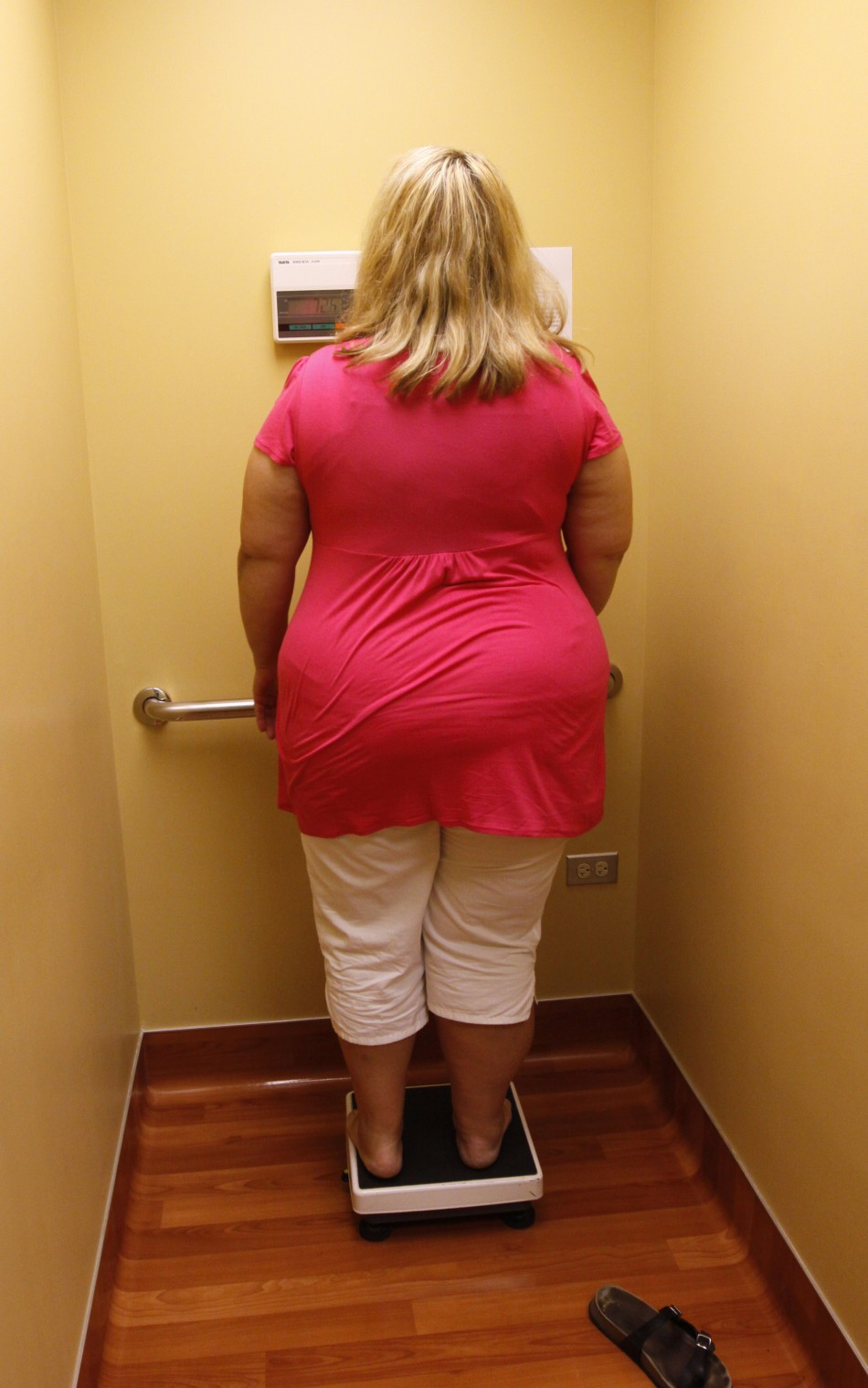 An obese woman looks at her weight - Reuters