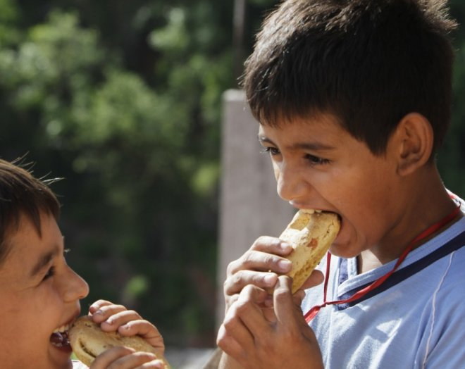 Paraguayan boys eat chipas during Easter Week celebrations in Asuncion