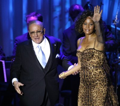 Singer Houston waves at the crowd next to Davis at conclusion of her performance at 2009 Grammy Salute to Industry Icons event in Beverly Hills