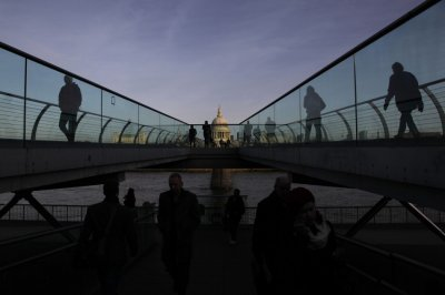 St Pauls Cathedral is seen during sunrise as pedestrians walk across the Millennium Bridge in the City of London