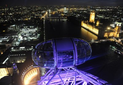 Passengers in a pod of the London Eye wheel view The Houses of Parliament and the centre of London at dusk
