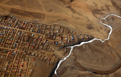 A frozen river is seen next to a group of houses located on the outskirts of the Mongolian capital city of Ulan Bator