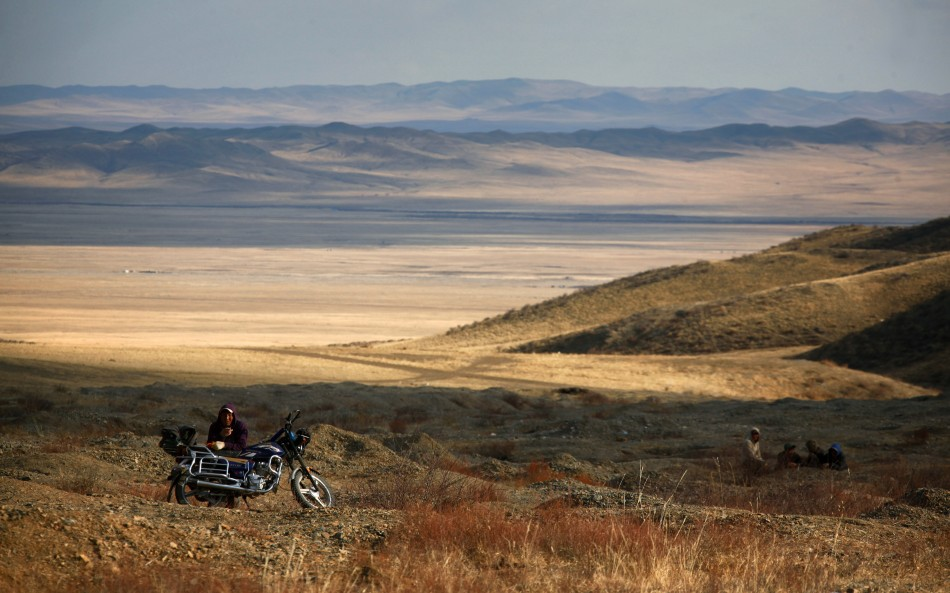 A small-scale miner takes a break from digging on hills surrounding grasslands located around 200km (62 miles) south-west of the Mongolian capital city Ulan Bator
