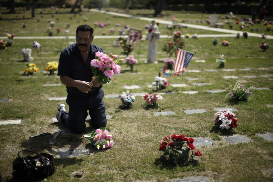 Man puts flowers on grave at pet cemetery in Huntington Beach