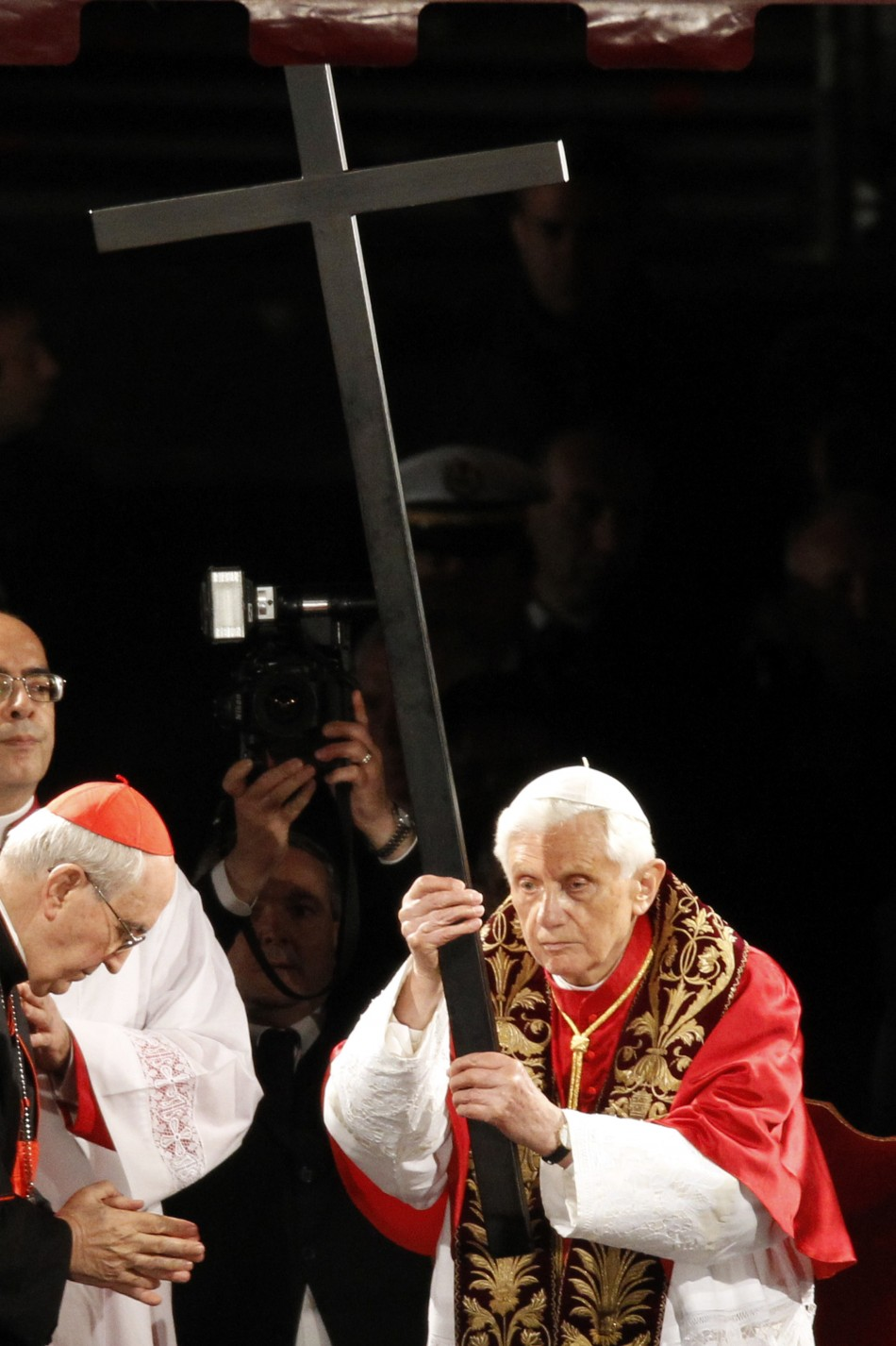 Pope Benedict XVI holds the cross as he leads the Via Crucis (Way of the Cross) procession at the Colosseum in downtown Rome