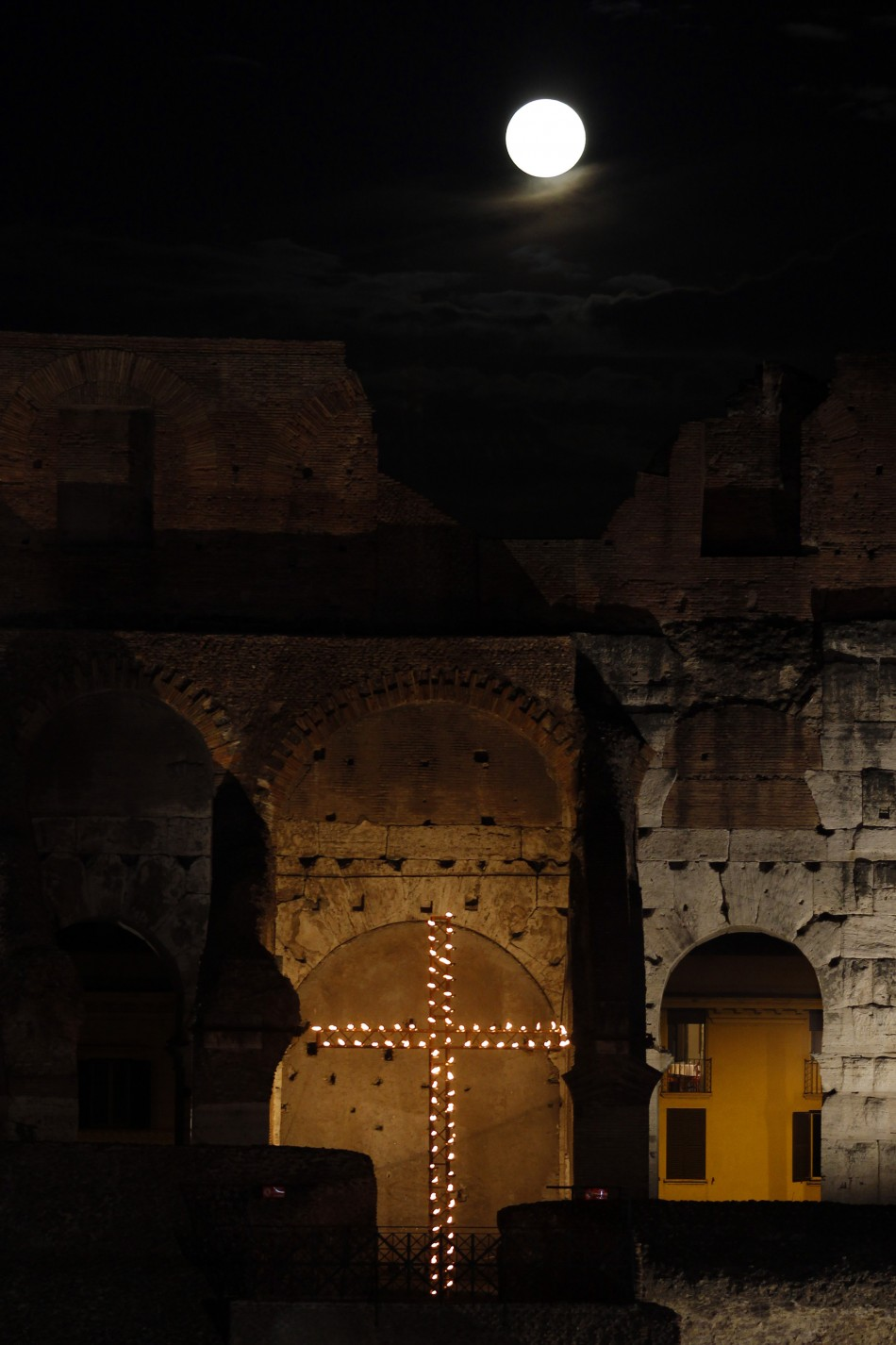 The full moon raises over the Colosseum before the Via Crucis Way of the Cross procession in downtown Rome