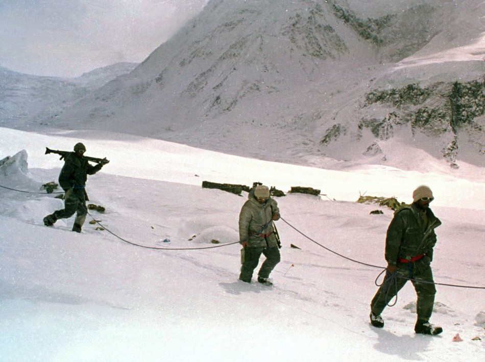 Pakistani soldiers, tied to each other for safety in hostile weather conditions, carry their weapons some time in June 1999 as they cross a snowy field on the Siachen Glacier in Pakistan.