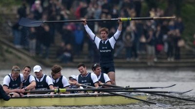 Moritz Hafner of Oxford stands up to celebrate defeating Cambridge in the 157th Boat Race on the River Thames in London