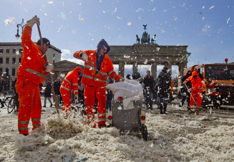 Municipal workers clean up feathers after pillow fight flashmob at Brandenburg Gate that in Berlin