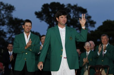 Bubba Watson of the U.S. receives his green jacket from 2011 champion Charl Schwartzel of South Africa after winning a playoff to become champion of the 2012 Masters Golf Tournament in Augusta