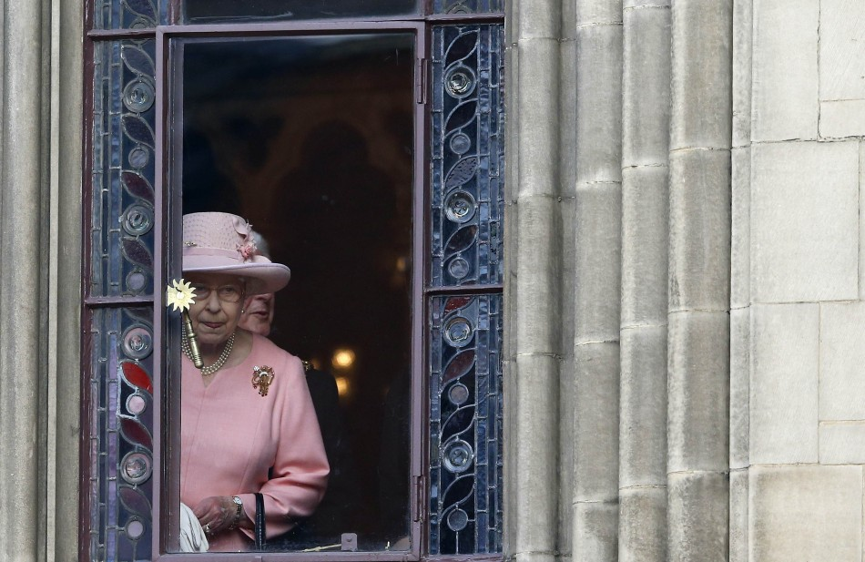 Britain's Queen Elizabeth looks out of a window during her visit to Manchester town hall in northern England