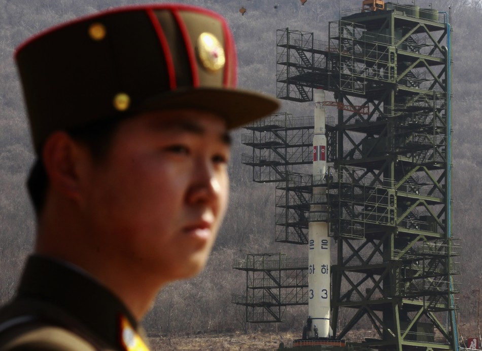 Soldier stands guard in front of Unha-3 rocket at West Sea launch site near Pyongyang