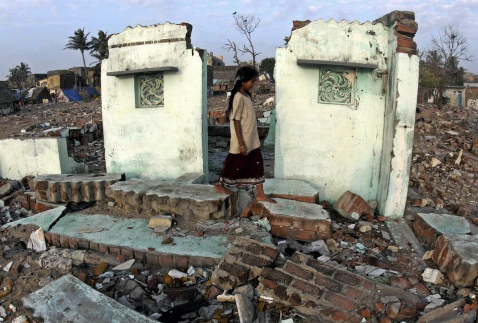 An Indian Ocean tsunami survivor walks amid the debris of her house at Marina beach in Chennai