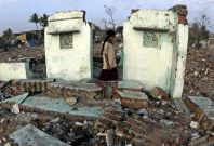 An Indian Ocean tsunami survivor walks amid the debris of her house at Marina beach in Chennai