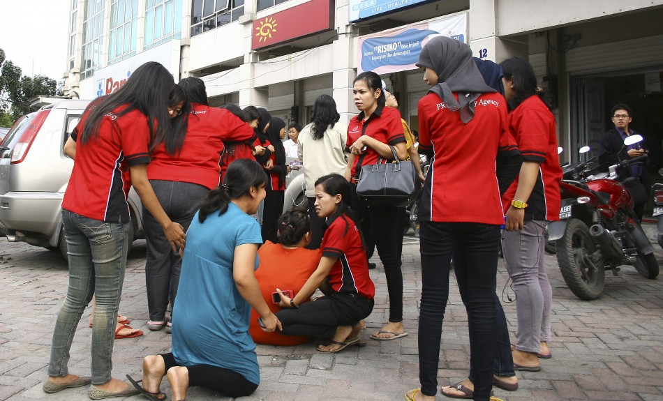 Office workers panic as they evacuate and gather in front an office building in Medan after an earthquake struck Indonesia