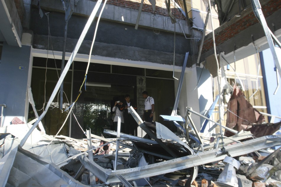 A security guard inspects the damage of a bank office in Indonesias province of Banda Aceh