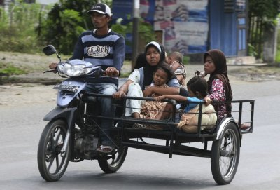 A man evacuates his family in a motorcycle in Banda Aceh after a strong earthquake struck Indonesia province