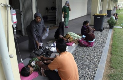 Patients rest in a corridor of a hospital after being evacuated from the hospital building in Banda Aceh, after an earthquake hit the western coast of Sumatra
