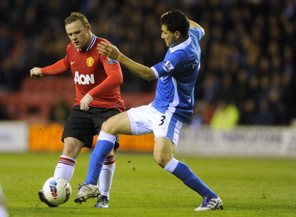 Wigan Athletic039s Alcaraz challenges Manchester United039s Rooney during their English Premier League soccer match at the DW Stadium Wigan